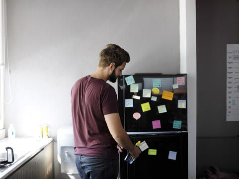 Picture of man taking a bottle out of a fridge