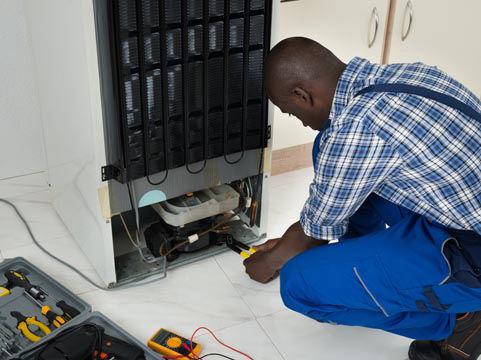 Picture of technician repairing a fridge freezer